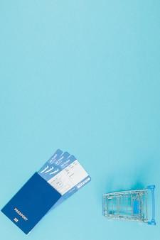 Boletos para aviones y pasaporte, y carrito de compras en una pared azul. copiar espacio para texto