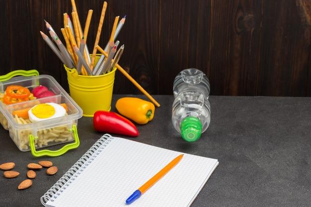 Bolígrafo amarillo en cuaderno con botella de agua y caja de lanzamiento.