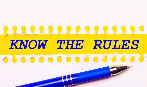 Bolígrafo azul y rayas blancas de papel rasgado sobre un fondo amarillo brillante con el texto conozca las reglas