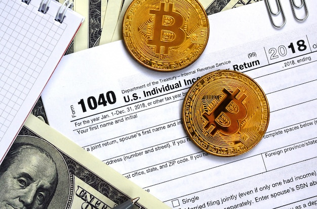El bolígrafo, los bitcoins y los billetes de dólar se encuentran en el formulario de impuestos 1040 de la declaración de impuestos de los ingresos de los estados unidos. el tiempo para pagar impuestos