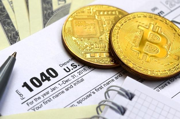 El bolígrafo, los bitcoins y los billetes de dólar se encuentran en el formulario de impuestos 1040 de estados unidos. el tiempo para pagar impuestos