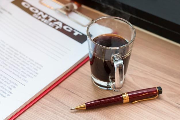Bolígrafo, café negro, documento de empresa y hoja de contacto.