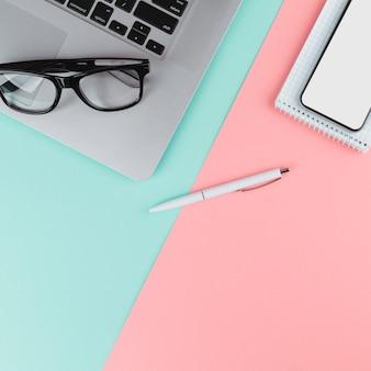 Bolígrafo cerca de bloc de notas, smartphone, gafas y portátil.