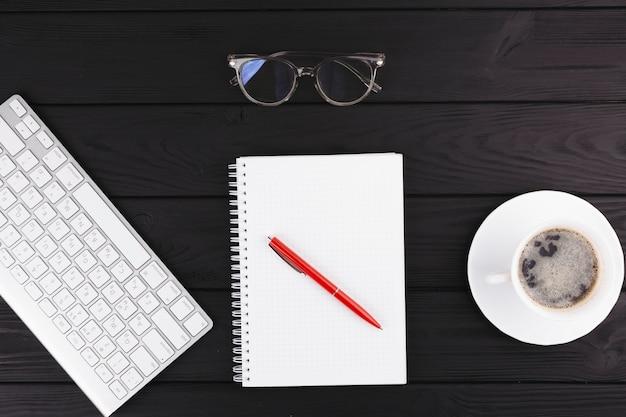 Bolígrafo cerca de bloc de notas, taza en platillo, lentes y teclado