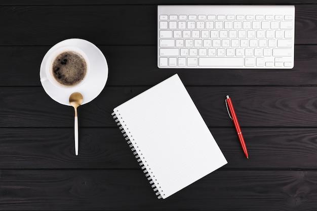 Bolígrafo cerca de libreta, taza en platillo, cuchara y teclado