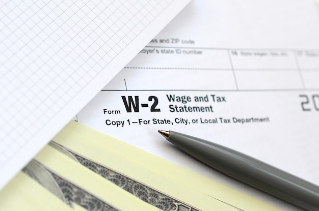 El bolígrafo, el cuaderno y los billetes de dólar se encuentran en el formulario de impuestos w-2 declaración de salarios e impuestos. el tiempo para pagar impuestos
