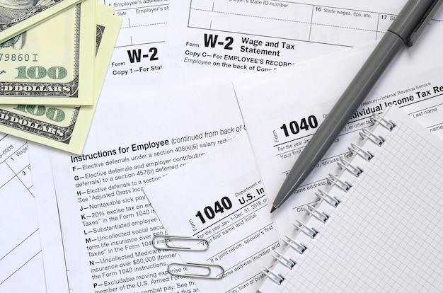El bolígrafo, el cuaderno y los billetes en dólares se encuentran en el formulario de impuestos 1040 de estados unidos. el tiempo para pagar impuestos