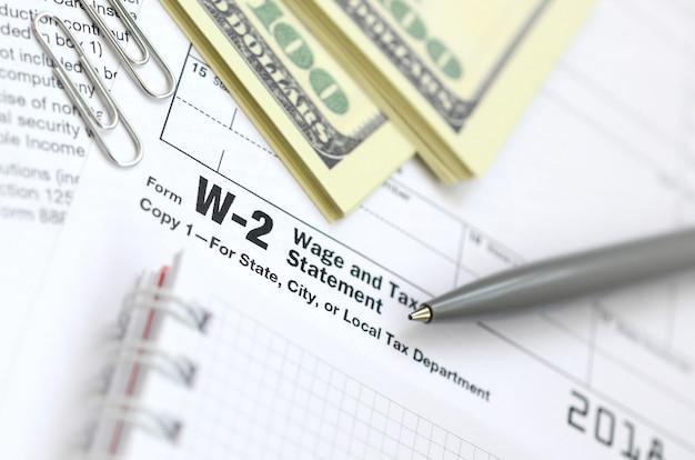 El bolígrafo, el cuaderno y los billetes en dólares se encuentran en el formulario de impuestos w-2 declaración de salarios e impuestos. el tiempo para pagar impuestos