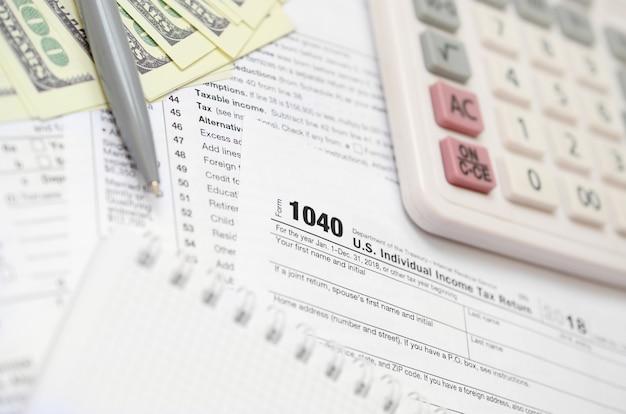 El bolígrafo, el cuaderno, la calculadora y los billetes en dólares se encuentran en el formulario de impuestos 1040 ee.