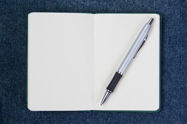 Bolígrafo en un cuaderno limpio. en una pared azul