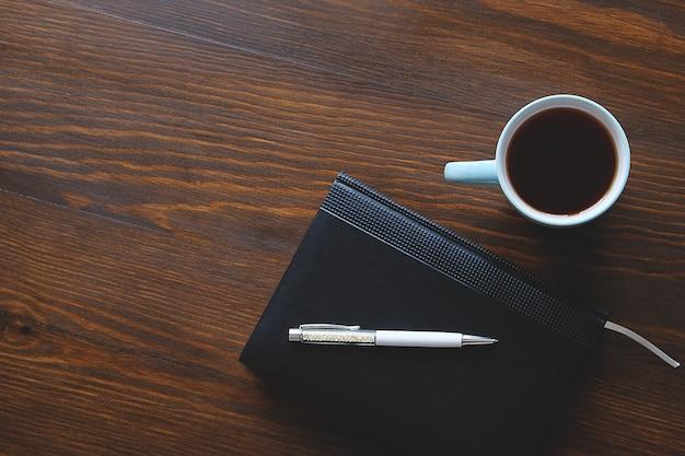 Bolígrafo, cuaderno o diario, una taza de té o café en una mesa de madera.