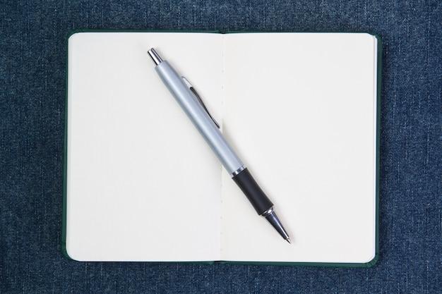 Bolígrafo en el cuaderno. en una pared azul