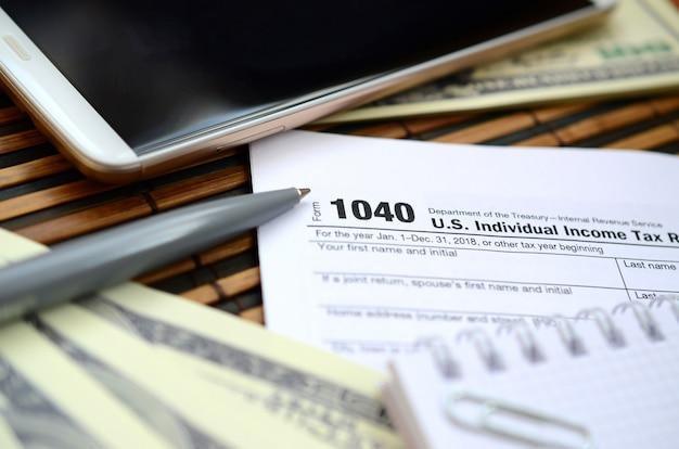 El bolígrafo, el cuaderno, el teléfono inteligente y los billetes en dólares se encuentran en el formulario de impuestos 1040 de estados unidos. el tiempo para pagar impuestos