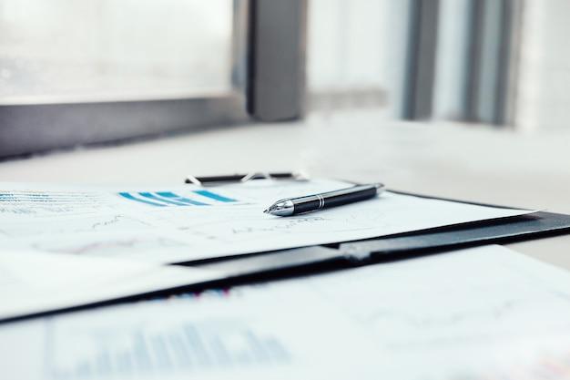Bolígrafo y documentos financieros en el escritorio