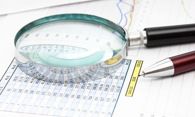Bolígrafo, lupa y el documento de trabajo con un diagrama