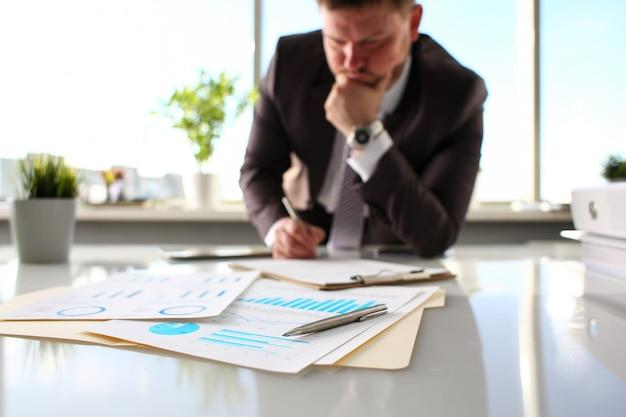 Bolígrafo plateado en papel importante sobre la mesa en la oficina