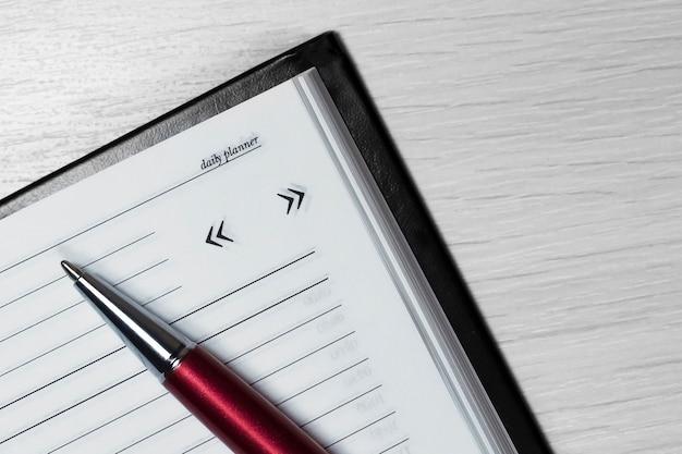 Bolígrafo rojo plateado en cuaderno abierto. agenda empresarial.
