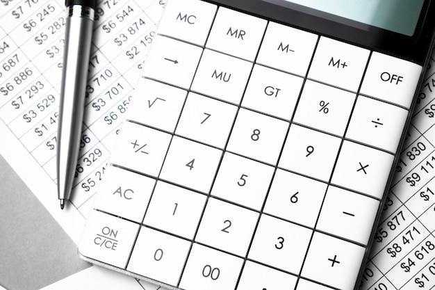 Bolígrafo, tabla de números y calculadora blanca