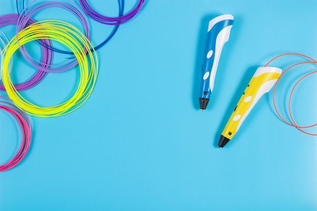 Bolígrafos 3d con filamento de plástico colorido en mesa azul
