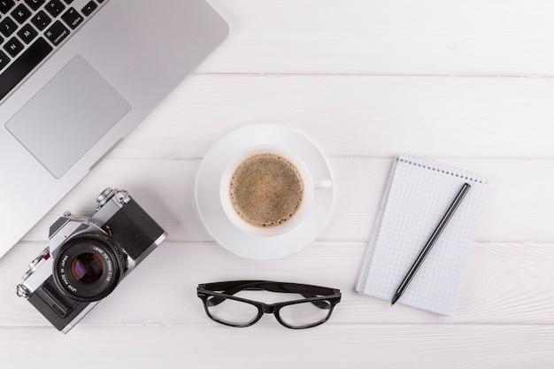Bolígrafos cerca de bloc de notas, cámara, gafas, taza y portátil