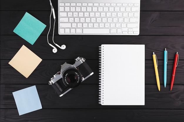 Bolígrafos cerca de cuaderno, cámara, auriculares, papeles y teclado.