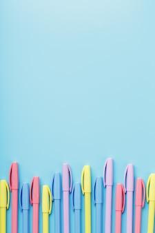 Bolígrafos multicolores en azul con espacio libre.