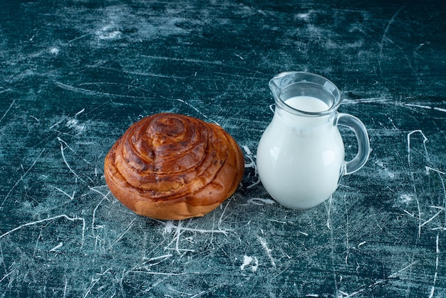 Un bollo de canela con un tarro de leche a un lado.
