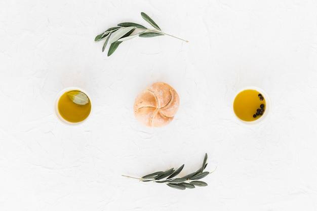 Bollo entre los cuencos de pimienta negra y aceite de oliva sobre fondo blanco
