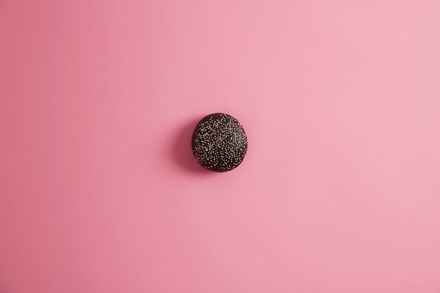 Bollo de pan gourmet negro para hacer sándwich adornado con semillas de sésamo, aislado sobre fondo rosa. comida chatarra y concepto de nutrición poco saludable. hamburguesa casera. delicioso refrigerio, comida rápida.