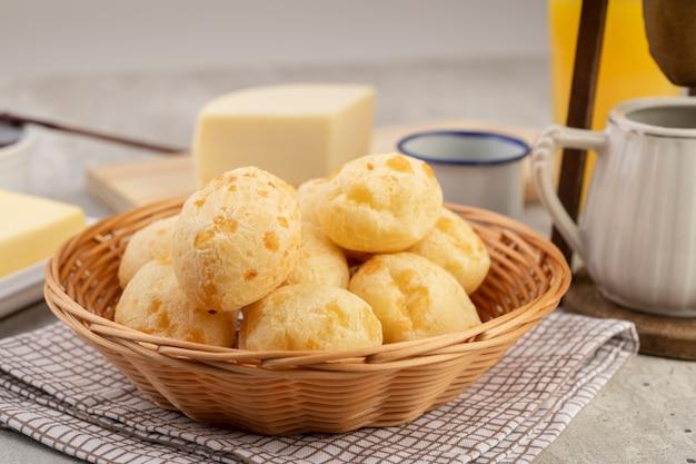 Bollo de queso típico brasileño en un bol, café, mantequilla y jugo de naranja.