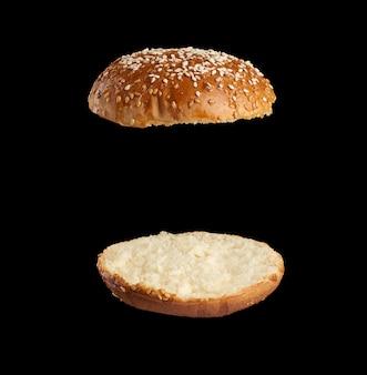 Bollo redondo de semillas de sésamo al horno cortado por la mitad, mitades fritas y levitando en el aire una sobre la otra, espacio negro