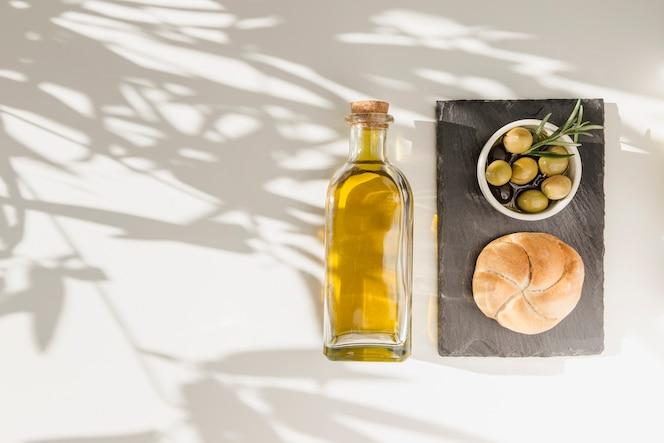 Bollo y aceitunas en un tazón con botella de aceite en la sombra cayendo sobre el fondo blanco