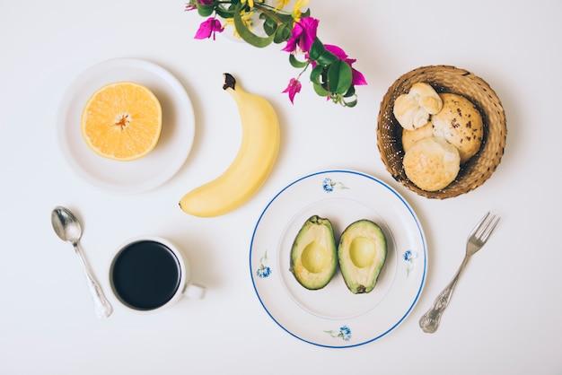 Bollos al horno aguacate; plátano; naranja a la mitad; café y flores sobre fondo blanco.