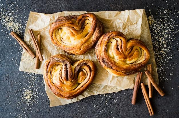Bollos de canela fragantes frescos al horno. pasteles caseros tradicionales sobre fondo oscuro.
