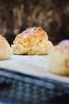 Bollos dulces caseros con miel en la rejilla del horno sobre una superficie clara. copia espacio