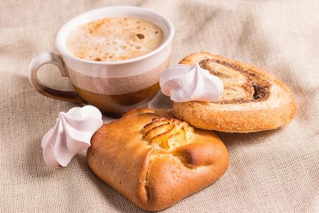 Bollos dulces, merengues y taza de café en una tabla de madera