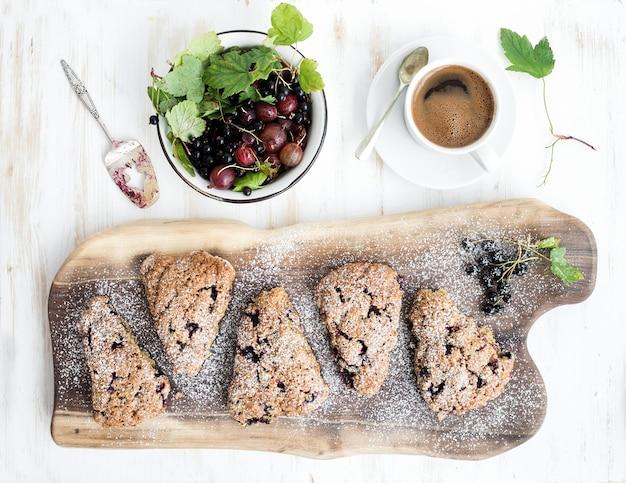 Bollos frescos de grosella negra con café y tazón de bayas sobre tabla de madera rústica de nogal, vista superior