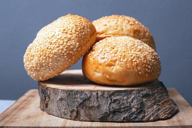 Bollos para hacer hamburguesas con semillas de sésamo en un soporte de madera sobre un fondo gris close-up.