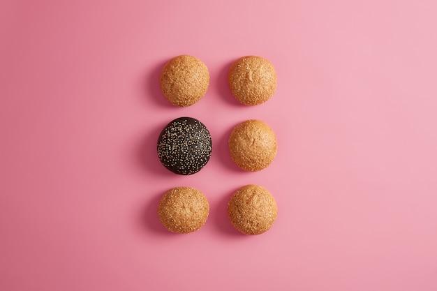 Bollos de hamburguesa fresca con semillas de sésamo dispuestas en dos filas sobre un fondo rosado. preparación de comida rápida o hamburguesa casera. fotografía gastronómica. alimentación o dieta poco saludables. brioches suaves redondos. enfoque selectivo