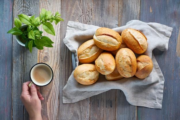 Bollos de pan en canasta de madera rústica, hojas de primavera y mano con taza de café
