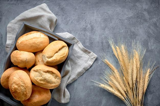 Bollos de pan en la cesta de madera rústica con espigas, vista superior en gris