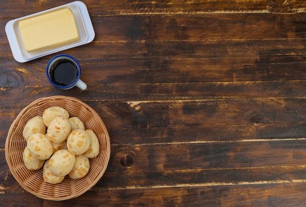 Bollos de queso típicos brasileños en una canasta, mantequilla y café con espacio de copu