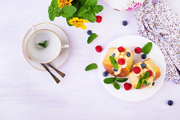 Bollos savares de ron decorados con crema batida y bayas frescas