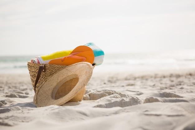 Bolsa con accesorios de playa sobre la arena mantuvo