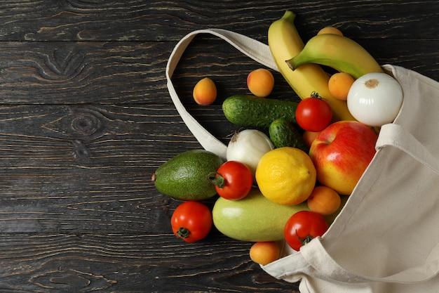 Bolsa de algodón con verduras y frutas en mesa de madera
