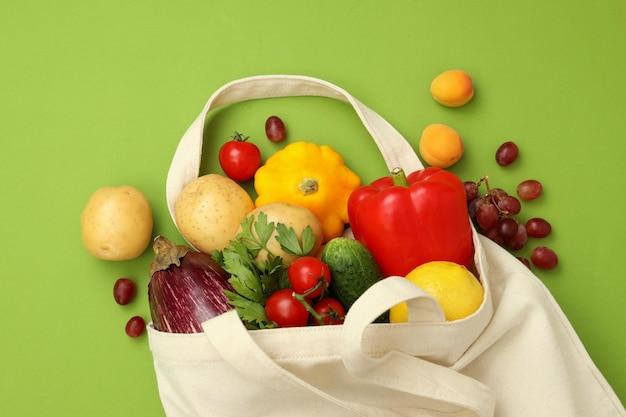 Bolsa de algodón con verduras y frutas sobre fondo verde