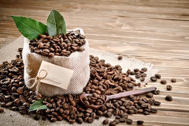 Bolsa de arpillera llena de granos de café sobre fondo de madera.