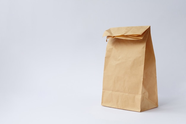 Bolsa artesanal de papel marrón para ir de compras sobre fondo blanco.