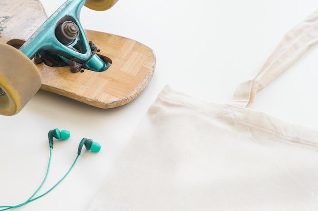 La bolsa de asas, el monopatín y el auricular blancos en blanco de lino en el fondo blanco