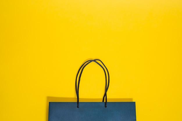 Bolsa azul con asas sobre un fondo amarillo aislado
